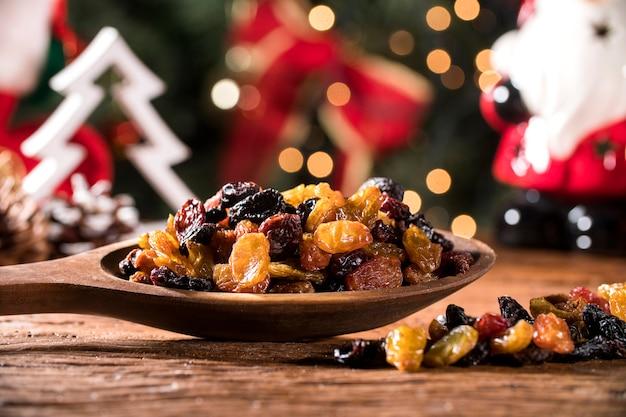 クリスマスの背景を持つ素朴な古い木製のテーブルの上にボウルにレーズン。