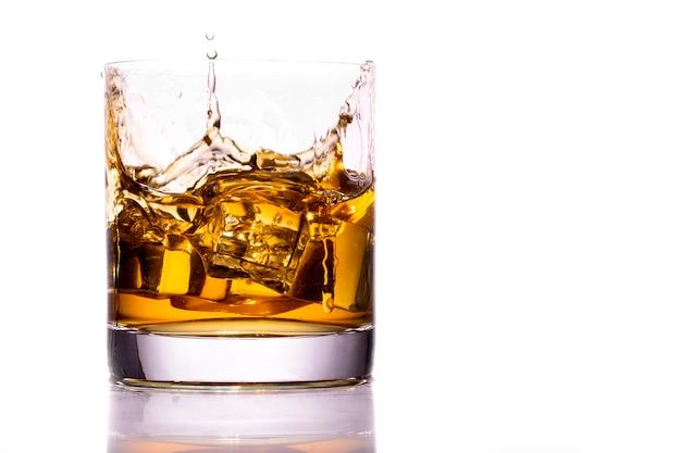 スプラッシュ、白い背景で隔離のウイスキーグラス