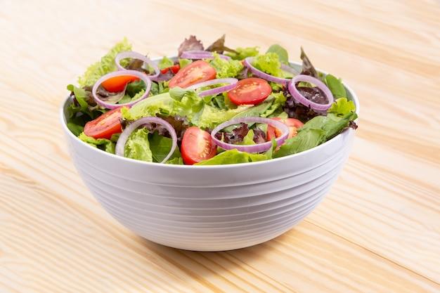Салат из свежих овощей с капустой, луком и помидорами в миске