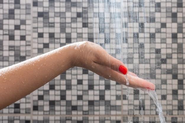 手とシャワーからの水滴のソフトセレクティブフォーカス
