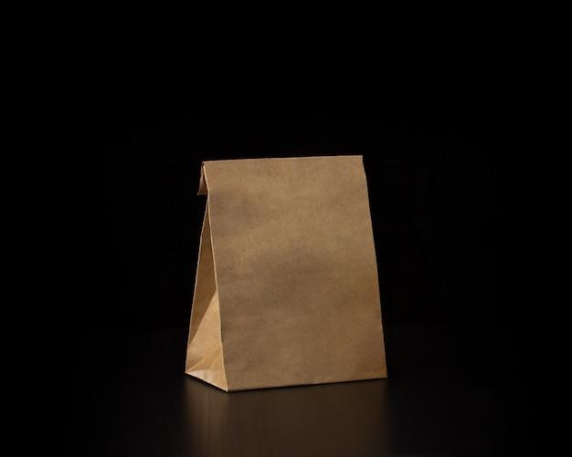 木製の背景の空白のクラフト紙袋。レスポンシブデザインのモックアップ。