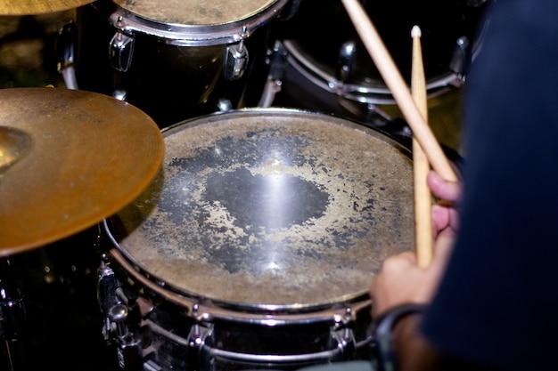 スティックとドラムのクローズアップとドラマーの手