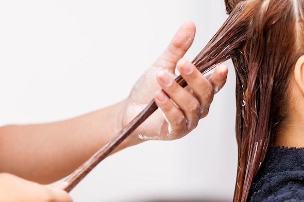 Парикмахер, применяя лечение волос. нанесение цветного крема на волосы.