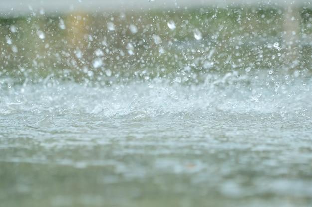 Капли дождя падают в большой луже на городской асфальт в городе.