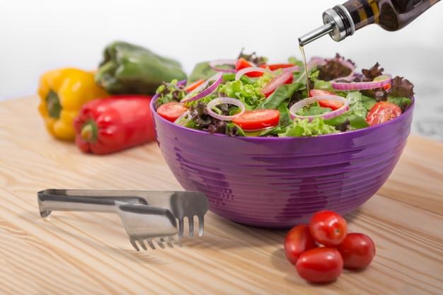 Салат из свежих овощей с капустой и морковью в миске с оливковым маслом