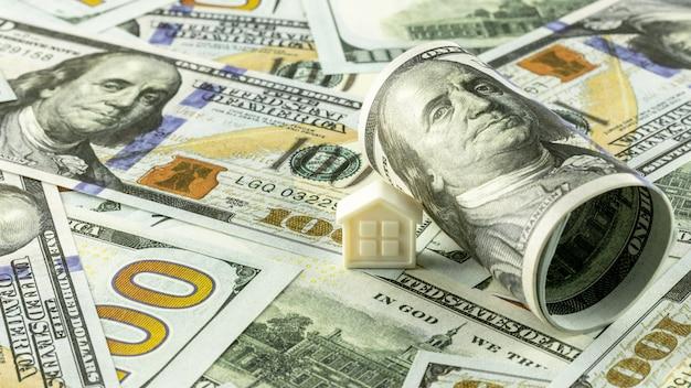 紙幣の山の上の小さな家。