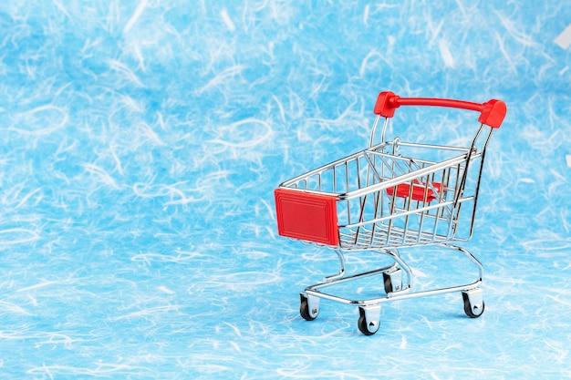 青い背景の空っぽのショッピングカート