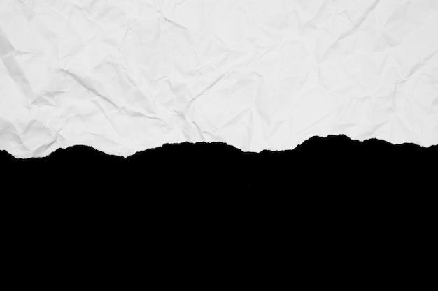 黒の背景に分離されたホワイトペーパーのリッピング