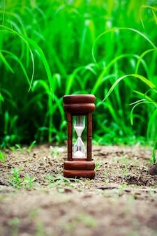 緑の芝生のフィールドで小さな砂時計。 - 通過時間と期限までのカウントダウンを測定します。