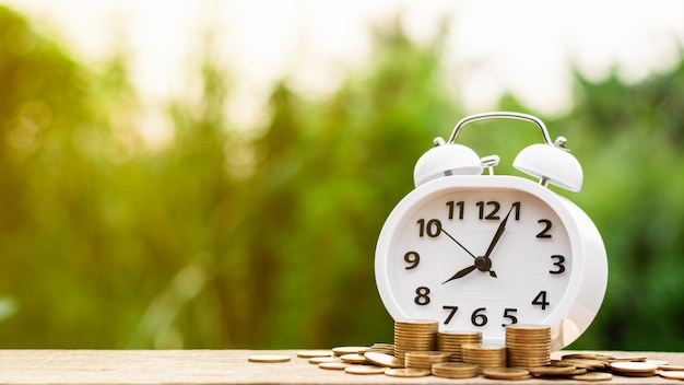 レトロな目覚まし時計とテーブルの上の黄金のコインの山。