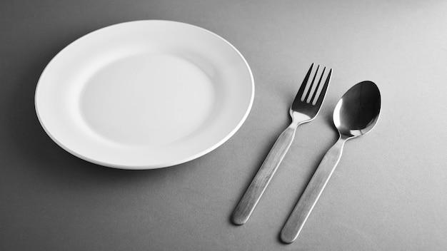 フォーク、スプーン、白いセラミック料理