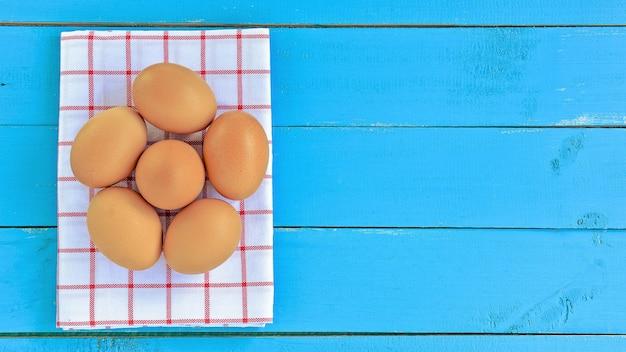 Группа яйца на синем деревянном столе - фон