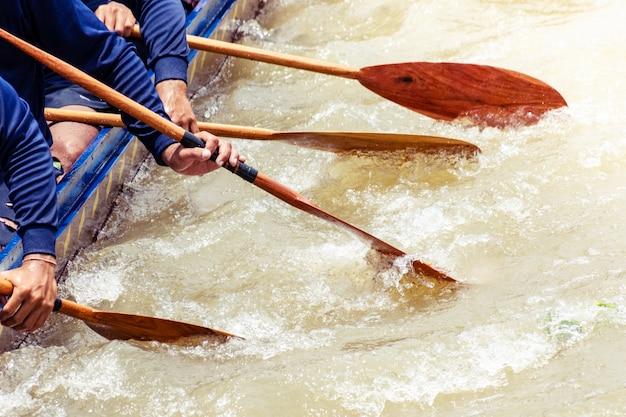 人の手のクローズアップは、ローイングレースでボートしています