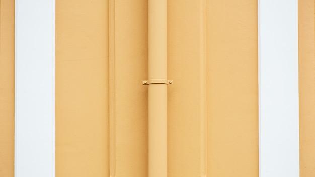 水配管システムは薄いオレンジ色のコンクリート壁と取付ける