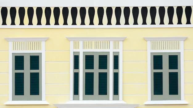淡い黄色のコンクリートの建物で古典的な木製の窓