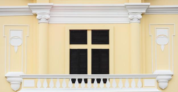 淡いオレンジ色のコンクリートの建物で古典的な木製の窓