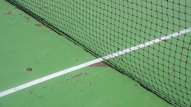 緑のセメントコートに黒いテニスネット