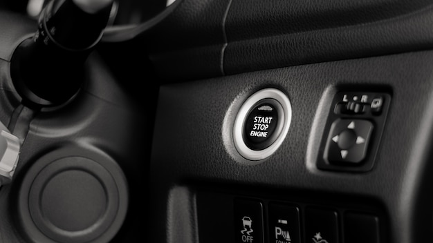 車のエンジン始動/停止ボタンを押すのクローズアップ。