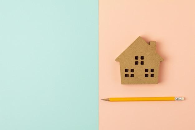 茶色の木の家のアイコンと青とピンクの背景に鉛筆