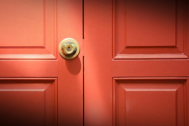 赤い木製ドアの真鍮製ドアハンドル
