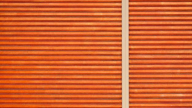 パターンとオレンジ色のヴィンテージの金属製のドアの線