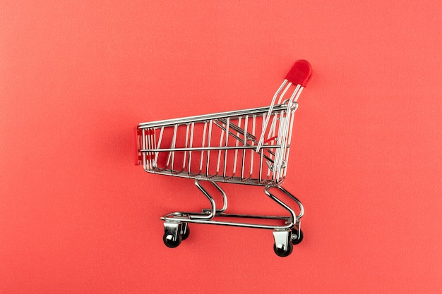 ピンクの背景の空っぽのショッピングカート