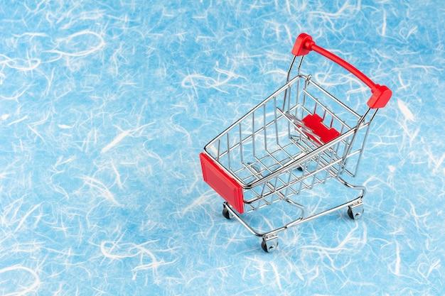 青い背景の空っぽのショッピングカート。