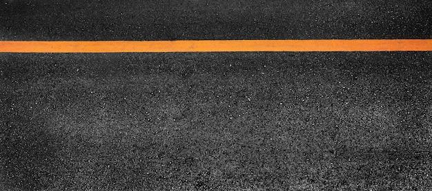 黒いアスファルトの上の黄色のペンキライン。宇宙輸送の背景