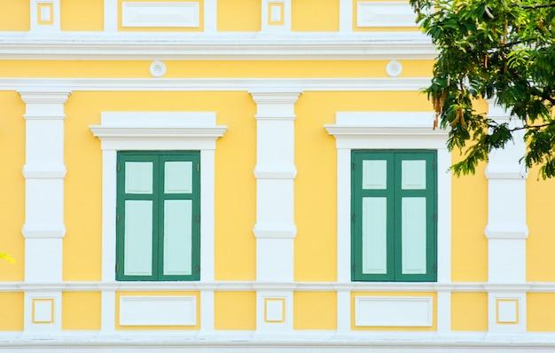黄色のコンクリートの建物で古典的な木製の窓