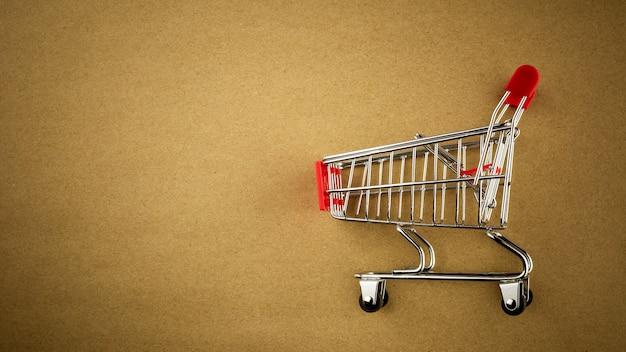 茶色の紙の背景に空のショッピングカート
