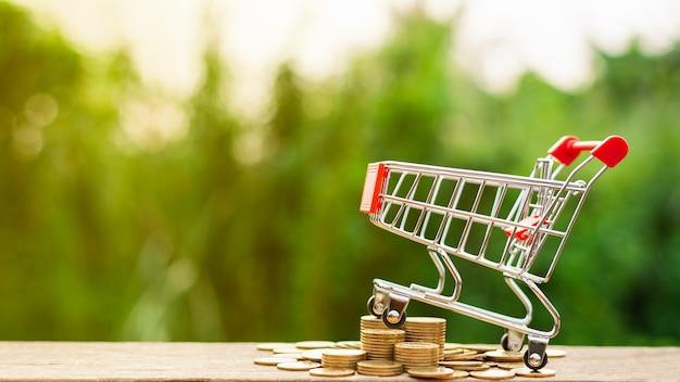 ショッピングカートと木のテーブルに黄金のコインの山