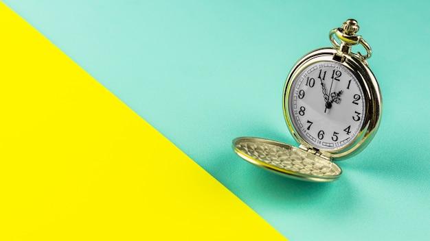 黄色と青の背景に古い懐中時計