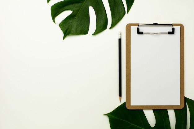 ホワイトオフィスデスクの背景にクリップボードとホワイトペーパー。フラットレイアウトデザイン。
