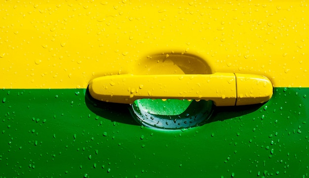 Желтая и зеленая автомобильная дверь в дождь день - крупным планом