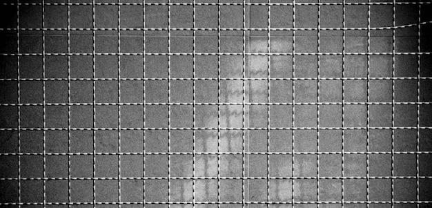 石の壁の背景に影を持つケージメタルワイヤー