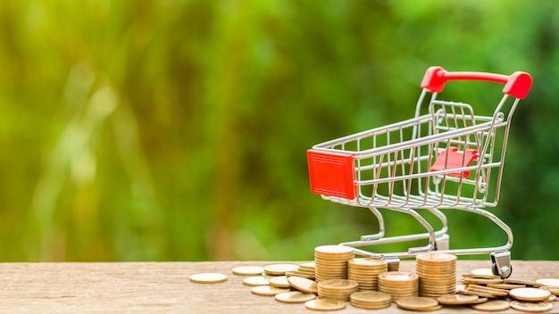 空っぽのショッピングカートと木のテーブルに黄金のコインの山。
