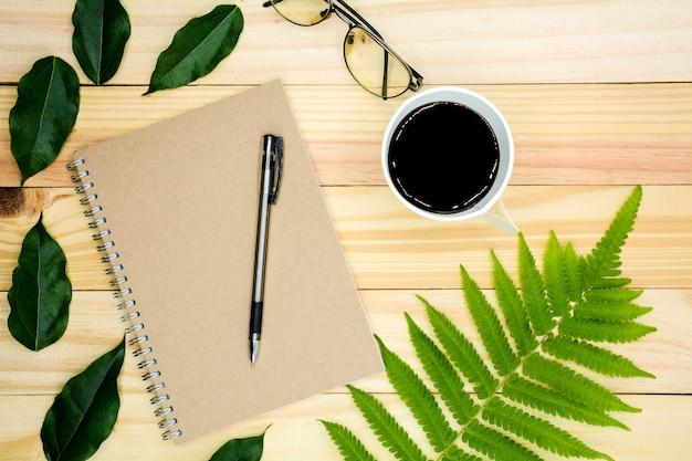 木製のテーブルの上の緑の葉の本