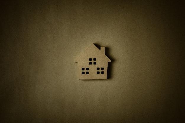 茶色のリサイクル紙の背景に茶色の木の家のアイコン