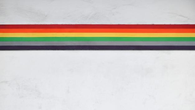 古い白いコンクリートの壁に虹の描かれた