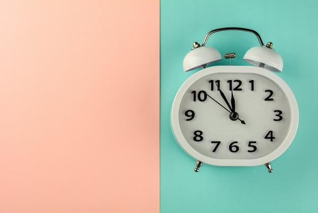 ピンクとブルーの背景に白のビンテージの目覚まし時計。 - 上面図。