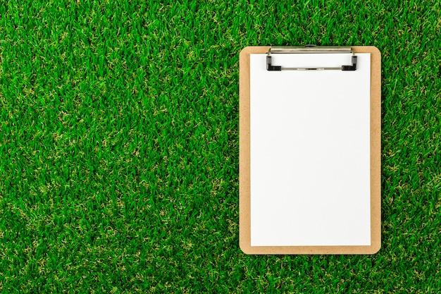 朝の緑の芝生の上のクリップボードとホワイトペーパー。