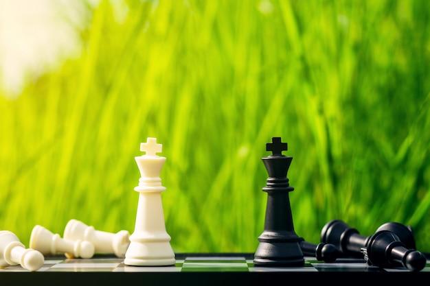 白と黒のキングチェスがチェス盤上で遭遇します。 - リーダーとビジネスの勝者の概念。