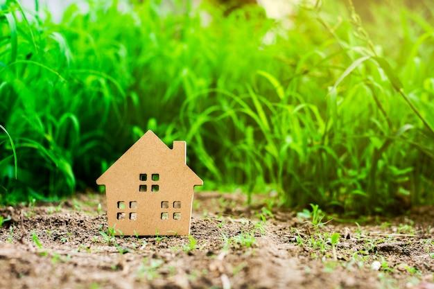 緑の芝生のフィールドで小さなモデルハウス。 - 家族、不動産、事業投資の概念のためのローン。