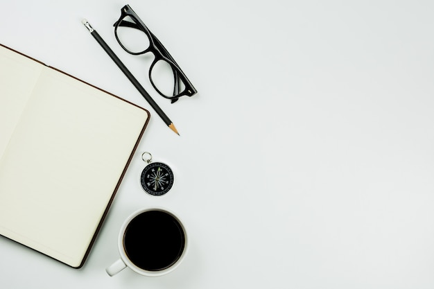 Коричневая кожаная тетрадь и кофейная чашка на белой предпосылке стола с космосом экземпляра.