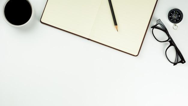 茶色の革ノートとコピースペースを持つ白い机の背景にコーヒーカップ。 - 事務用品や教育のコンセプト。