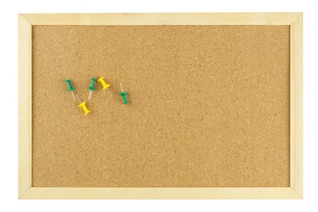 木製フレームの空白のコルク板に黄色と緑の押しピン