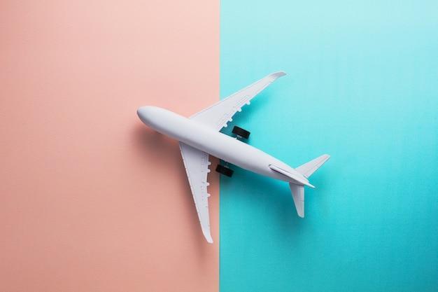 Модель самолета на розовом и голубом пастельном цветовом фоне.
