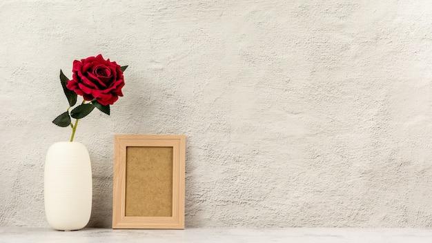 Классическая деревянная фоторамка и красная роза в вазе