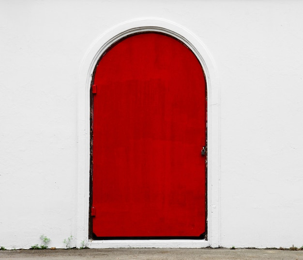白いコンクリートの壁にアンティークの赤いドア