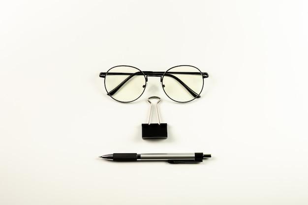 メガネ、スタンプペーパークリップ、白い背景の上のペン